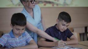 Helfende Kinder des Lehrers Schul, dietest in Klassenzimmer schreiben Ausbildung, Volksschule, Lernen und Leutekonzept stock footage