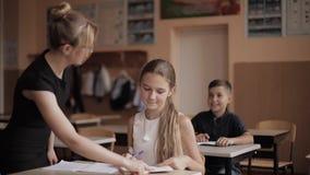 Helfende Kinder des Lehrers Schul, dietest in Klassenzimmer schreiben Ausbildung, Volksschule, Lernen und Leutekonzept stock video footage