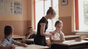 Helfende Kinder des Lehrers Schul, dietest in Klassenzimmer schreiben Ausbildung, Volksschule, Lernen und Leutekonzept stock video
