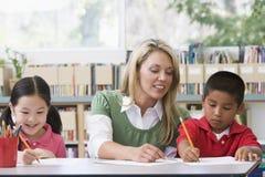 Helfende Kursteilnehmer des Lehrers mit Schreibensfähigkeiten Lizenzfreie Stockfotos