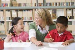 Helfende Kursteilnehmer des Lehrers mit Schreibensfähigkeiten Stockbild