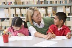 Helfende Kursteilnehmer des Lehrers mit Schreibensfähigkeiten Lizenzfreie Stockfotografie