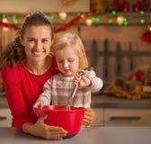 Helfende Mutter des Babys machen Weihnachtsplätzchen Lizenzfreies Stockfoto
