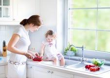 Helfende Mutter des netten Kleinkindmädchens, zum des Gemüses zu kochen Lizenzfreies Stockfoto