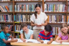Helfende Schüler des hübschen Lehrers in der Bibliothek stockfotos