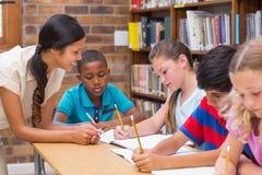 Helfende Schüler des hübschen Lehrers in der Bibliothek lizenzfreie stockfotos