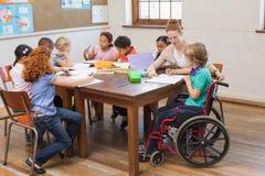 Helfende Schüler des hübschen Lehrers im Klassenzimmer Lizenzfreie Stockfotos