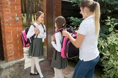 Helfende Tochter der jungen Mutter, zum des Rucksacks bevor dem Gehen zur Schule an zu setzen Stockbild
