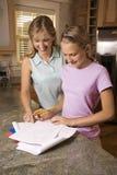 Helfende Tochter der Mammas mit Heimarbeit. Stockfotografie