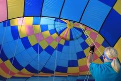 Helfende Zugschnüre der jungen Frau, während Ballone mit Heißluft, Ballonfestival, Queensbury, New York gefüllt werden, im Septemb Lizenzfreie Stockbilder