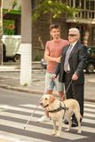 Helfender Blinder des jungen Mannes mit Blindenhund Stockfotos