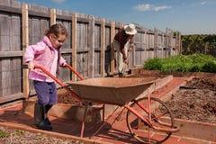 Helfender Großvater des Mädchens im Gemüsegarten lizenzfreie stockfotografie