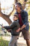 Helfender Junge des Vaters bei der Fischerei im Wald Lizenzfreies Stockfoto
