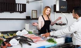 Helfender Kunde des Verkäufers in der Fischerei Lizenzfreie Stockfotografie