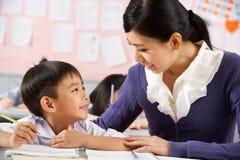 Helfender Kursteilnehmer, der am Schreibtisch in der chinesischen Schule arbeitet Lizenzfreie Stockfotos