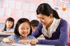 Helfender Kursteilnehmer, der am Schreibtisch in der chinesischen Schule arbeitet Stockfoto