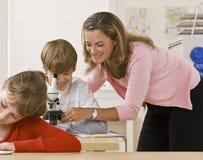Helfender Kursteilnehmer des Lehrers mit Mikroskop lizenzfreies stockbild