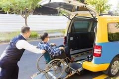 Helfender Mann des Fahrers auf dem Rollstuhl, der in Taxi kommt Stockfotos
