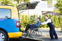 Helfender Mann des Fahrers auf dem Rollstuhl, der in Taxi kommt Stockfoto