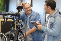 Helfender Mann des Verkäufers, zum des rechten Fahrrades zu kaufen lizenzfreie stockfotografie