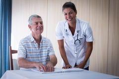 Helfender Patient der Ärztin, wenn das Blindenschrift-Buch gelesen wird Stockbild