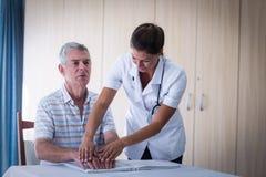 Helfender Patient der Ärztin, wenn das Blindenschrift-Buch gelesen wird Stockfoto