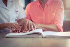 Helfender Patient der weiblichen Krankenschwester, der das Blindenschrift-Buch liest Stockbilder