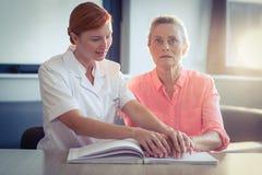 Helfender Patient der weiblichen Krankenschwester, wenn das Blindenschrift-Buch gelesen wird Stockfotografie