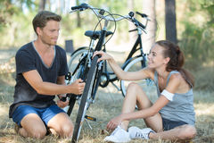 Helfender Radfahrer mit Reifenpannen Lizenzfreie Stockfotografie