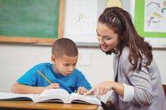 Helfender Schüler des hübschen Lehrers an seinem Schreibtisch lizenzfreies stockbild