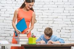 Helfender Student des Lehrers mit schwieriger Aufgabe in der Schule stockfoto