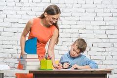 Helfender Student des Lehrers mit schwieriger Aufgabe in der Schule lizenzfreies stockbild
