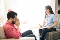 Helfender und advicing deprimierter Patient des Psychologen Stockbilder