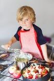 Helfender und backender Apfelkuchen des entzückenden kleinen Jungen in Haupt'' s-kitc lizenzfreies stockfoto