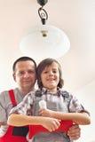 Helfender Vater des Sohns, der eine Glühlampe ändert Stockbilder