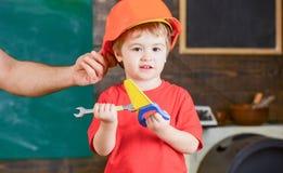 Helfender Vati der kleinen Arbeitskraft in der Werkstatt Kind, das mit Spielzeughandsaw und -schlüssel spielt Vater, der an Schut Lizenzfreies Stockfoto