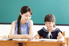 Helfendes Kind des jungen Lehrers mit Schreibenslektion lizenzfreies stockfoto