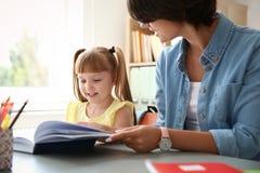 Helfendes Kind des weiblichen Lehrers mit Aufgabe stockfoto