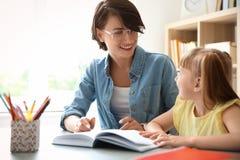 Helfendes Kind des weiblichen Lehrers mit Aufgabe lizenzfreie stockbilder