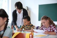 Helfendes Kind des weiblichen Lehrers mit Aufgabe stockfotografie