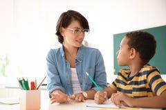 Helfendes Kind des weiblichen Lehrers mit Aufgabe lizenzfreies stockfoto