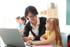 Helfendes Kind des weiblichen Lehrers mit Aufgabe lizenzfreies stockbild
