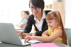 Helfendes Kind des weiblichen Lehrers mit Aufgabe stockbild
