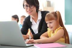 Helfendes Kind des weiblichen Lehrers mit Aufgabe stockbilder