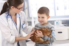 Helfendes Kleinkind des Tierarztes mit Kaninchen Lizenzfreie Stockfotos