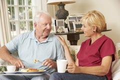 Helfer, der älteren Mann mit Mahlzeit im Pflegeheim dient Stockfoto