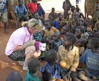 Helfer holt lächelnden afrikanischen Kindern im Dorf Uganda Hoffnung Stockbild