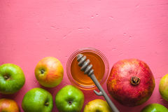 Helft-kader van appelen, granaatappel en honing voor het Joodse Nieuwjaar op een roze lijst Stock Foto's