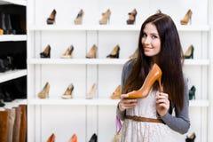 Helft-lengte portret die van vrouw hoog gehielde schoen houden royalty-vrije stock afbeeldingen