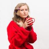 Helft-lengte portret vrij jonge huisvrouw die krulspelden en de kop thee van de omslagholding dragen royalty-vrije stock afbeelding